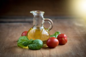 Fresh Basil, Tomato alongside Bottle of Oil